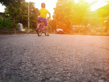 A boy standing with a bicycle in the middle of the road By waiting for his father to return home (picture blurred) Banque d'images - 132015183