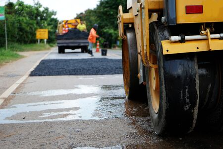 Réparer une route endommagée En ajustant le niveau avec de l'asphalte mélangé à de petites pierres Et ensuite compacté avec un compacteur vibrant Banque d'images