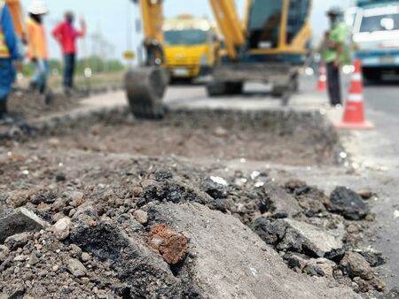 Blurred images, excavation of roads repaired using heavy machinery and human labor