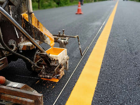 Workers are working Draw a yellow traffic line for safe road safety in thailand