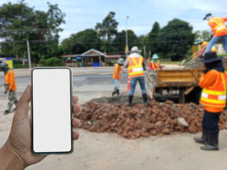 Blurred vision, excavation work and a phone in front.