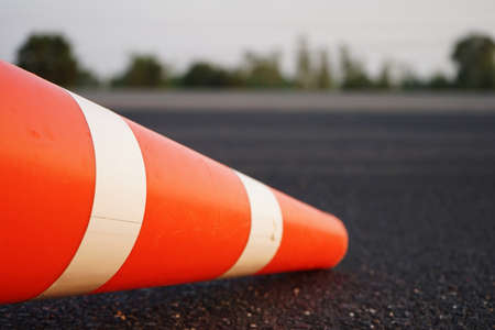 Red rubber cones are placed in the paved road. For safety on the road 免版税图像