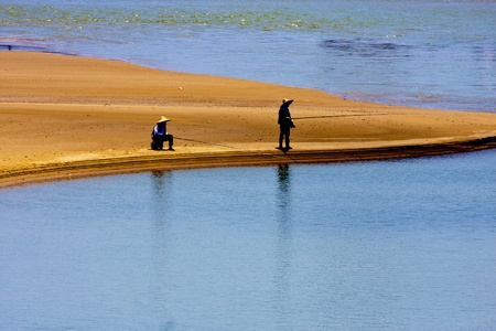 two people fishing at ocean on beach photo