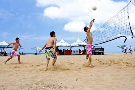 a group of people playing Beach volleyball on beach on May 31, 2011 in Fulong, Taiwan