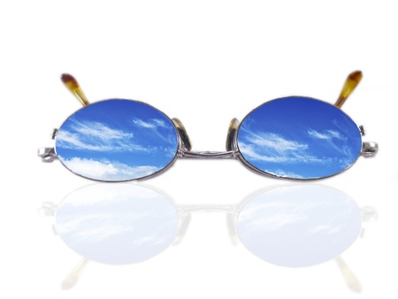Eyeglasses with blue sky and clouds reflected in the lenses - future vision metaphor Stock Photo - 9750240