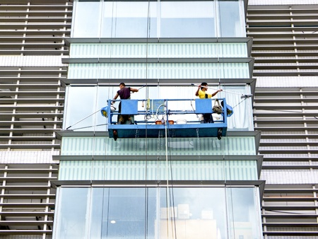 Taipei,Taiwan-June 28:two workers washing the windows of a skyscaper on June 28,2011 in Taipei,Taiwan