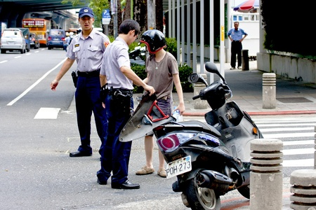 Taipei,Taiwan-July 4 two police men at the scene handle a car accident in Taipei city,2011 in Taipei,Taiwan Stock Photo - 9890688