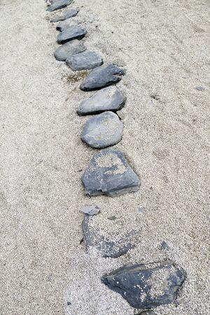 spread around: garden stone path with white sands spread around the rocks