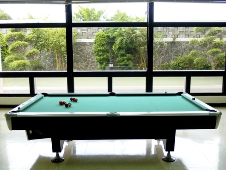 pool billiard tables in empty room near windows with plants photo