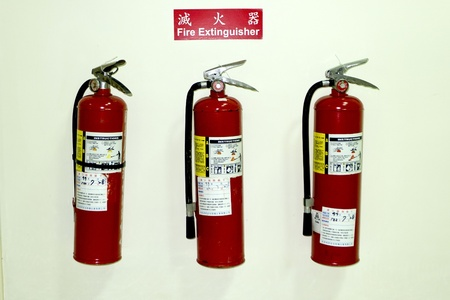 three fire extinguishers in row on white wall photo