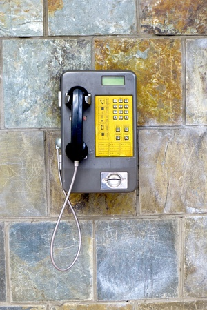 pay wall: public telephone on wall in a public modern stadium for communication