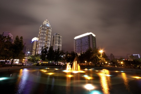 broad view of skyscraper modern building with fountains at night photo