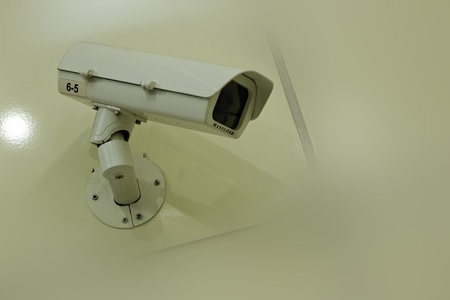 security camera on wall in public space photo