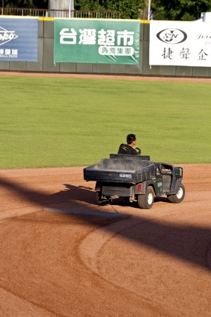 groundskeeper: Tianmu, Taiwan - September 1,2012 : a groundskeeper prepares infield before a baseball game,Sinon Bull vs Brother Elephant for the Chinese Professional Baseball League game on September 1, 2012 at Tianmu Stadium, Taipei, Taiwan.