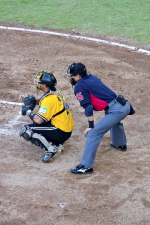 Tianmu, Taiwan - September 1,2012 : Hwang, a Brother Elephants catcher of CPBL, play ball for the Chinese Professional Baseball League game with referee on September 1, 2012 at Tianmu Stadium, Taipei, Taiwan.