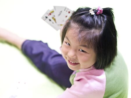 pokers: Close-up portrait of a beautiful cute girl playing pokers with smiling indoor Stock Photo