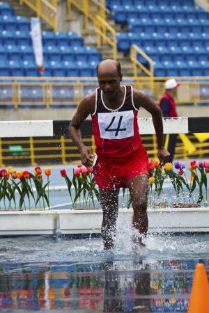 senior olympics: TAIPEI,TAIWAN -November 6,2012:3000m steeplechase man athlete in 17th Asia Master Athletics Championships in Taipei stadium on November 6,2012 in Taipei,Taiwan Editorial