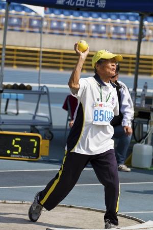 senior olympics: TAIPEI,TAIWAN -November 7,2012:man shot-put athlete in 17th Asia Master  Athletics Championships in Taipei stadium on November 7,2012 in Taipei,Taiwan