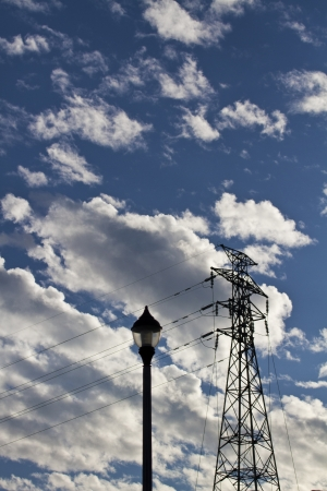 silhoutted electric high voltage power post against blue cloudy sky photo
