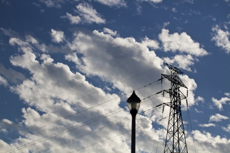 silhoutted: silhoutted electric high voltage power post against blue cloudy sky Stock Photo