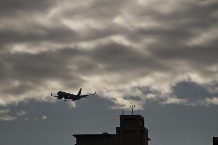 silhoutted: silhoutted airplane flying in the cloudy sky above a city Stock Photo