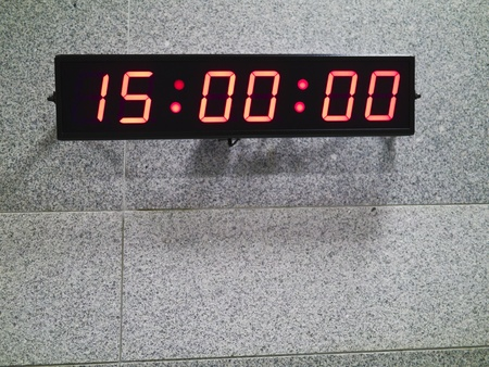 Digital clock on gray patterned wall photo