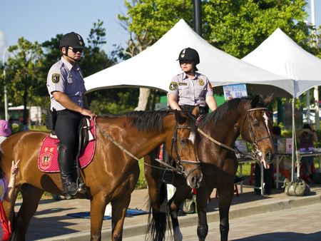 constable: New Taipei City , Taiwan : August 11 : the mounted police of Taiwan(R.O.C.) have a regular patrol in Fishers wharf in Tansui , August 11 , 2013 in New Taipei City,Taiwan