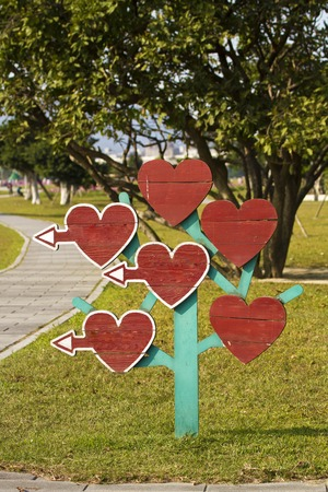 wooden heart blank billboard as direction indicator in park photo