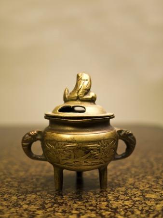 Antique incense burner on wooden table (Still life) photo