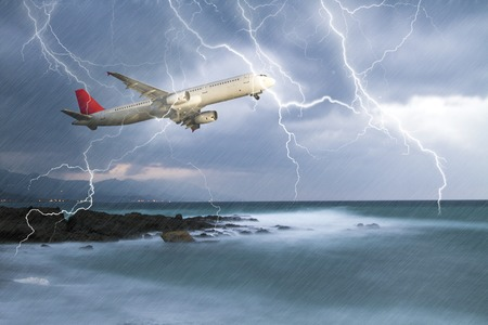 Passenger airplane travelling through rainy sky against stormy bolt cloudscape