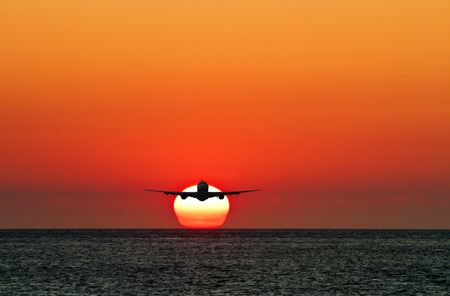silhoutted: silhoutted business passenger airplane in the air against sun Stock Photo