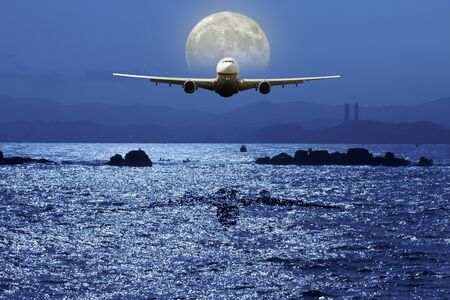 silhoutted: airplane fly above ocean under moonlight