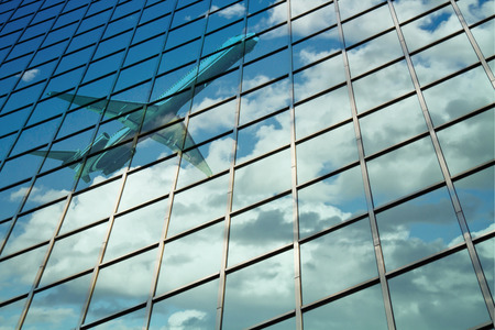 reflection: airplane reflect on a glass curtain wall with blue cloudy sky
