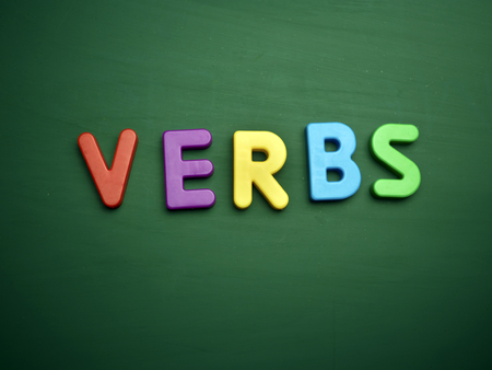 verbs: verbs concept in colorful letters isolated on blank blackboard