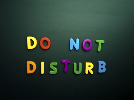 to disturb: do not disturb concept in colorful letters isolated on blank blackboard