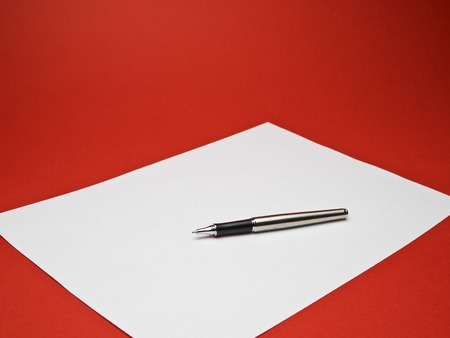 ball point: ball point silver pen on white paper with red background Stock Photo