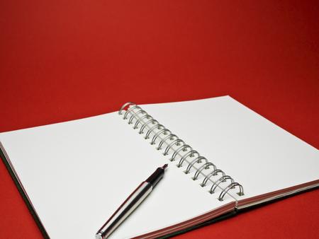 ball pens stationery: cuaderno de dibujo blanco con bol�grafo met�lico de plata sobre fondo rojo
