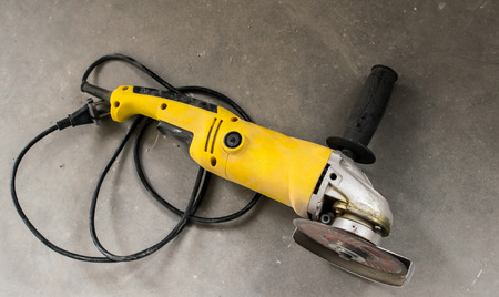 Dirty yellow angle grinder on a gray concrete photo
