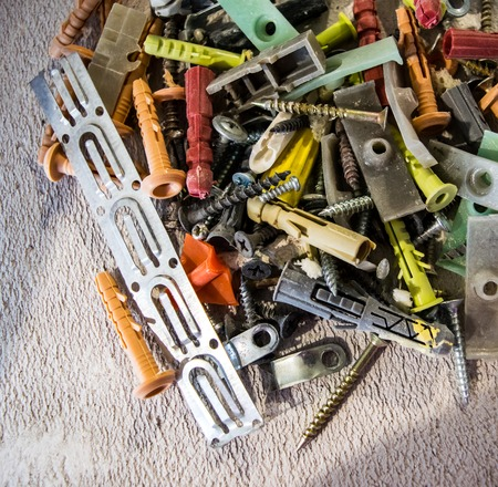 A large pile of nails, screws, anchors of different colours, metal plate  and other building elements photo