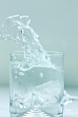 water splashing into a glass on white background  photo