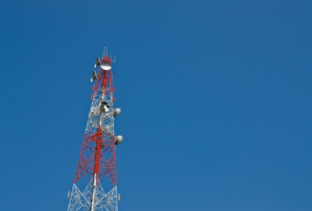 Modern cell and antenna with flat parabola on blue sky photo