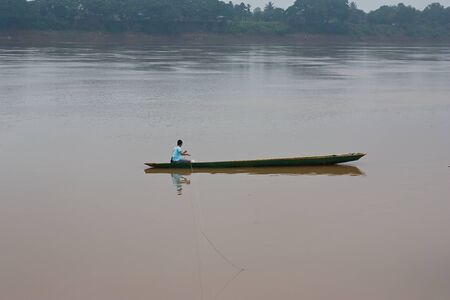 fisherman in a boat on a river in the morning  photo