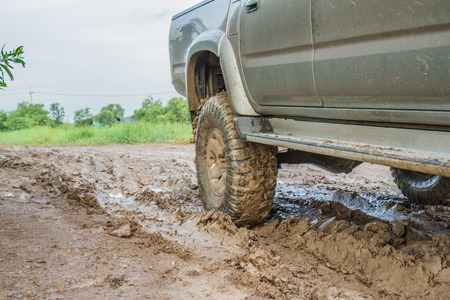 muddy tracks: BANGKOK -AUGUST 22: Toyota Sport cruiser Hilux 2.5L crossing obstacle at 4x4 track on August 22, 2014 in Pathum Thani, Bangkok, Thailand Editorial