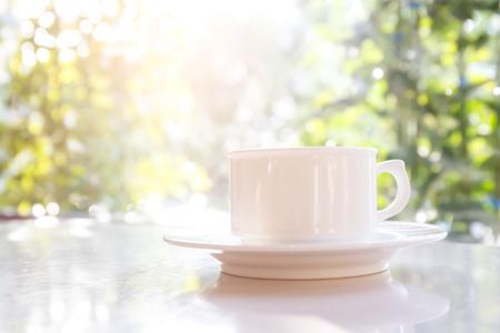 背景として太陽とテーブルの上の白いコーヒー カップ。 写真素材
