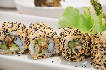 Maki Sushi - Roll with avocado,  Sesame outside.