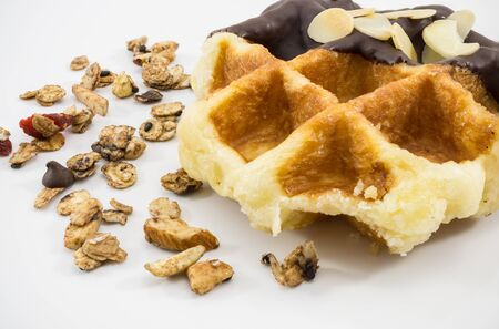 Waffles with chocolate, nut and granola on white background.