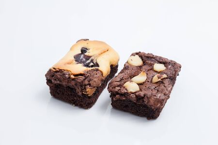 Chocolate brownie with macadamia on white background.
