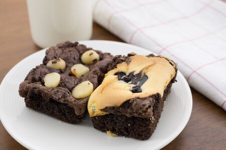 Chocolate brownie, macadamia, milk on wood table. Stock Photo