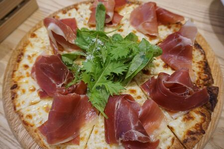 Sliced pizza with prosciutto (parma ham), arugula (salad rocket) and parmesan on wooden plate. Stock Photo