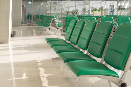 Empty airport terminal waiting area with chairs in morning time. Airport interior in waiting zone.